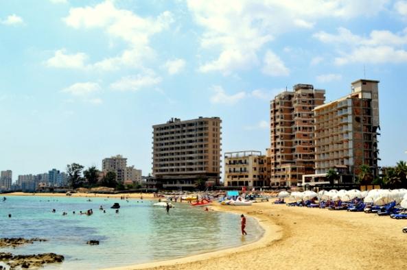 Pessoas pegando praia com uma cidade fantasma e prédios bombardeados ao fundo.